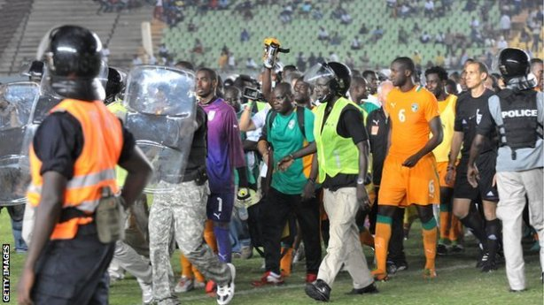 The Ivory Coast players being escorted from the pitch after crowd trouble in Dakar last November