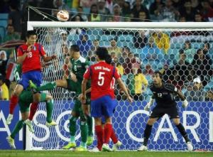 South Korea's Lee Jeong-hyeop heads the ball to score a goal against Iraq during their Asian Cup semi-final soccer match at the Stadium Australia in Sydney
